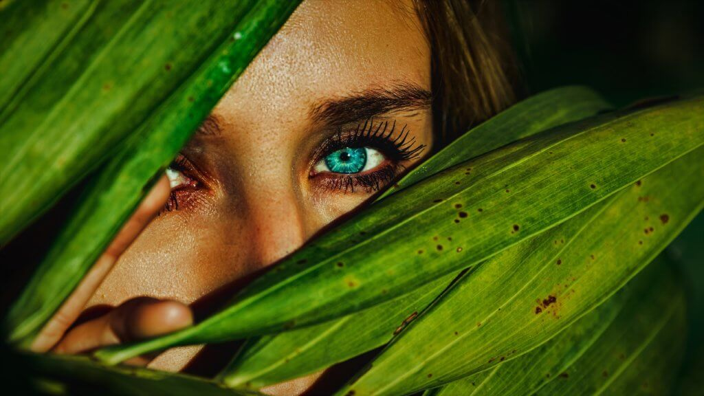 A woman face and eye peeking through the leaves of a plant