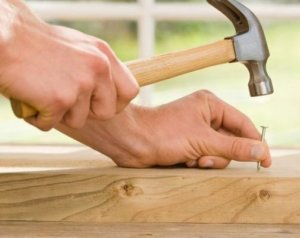 two hands holding a hammer and a nail to hammer into a board of wood